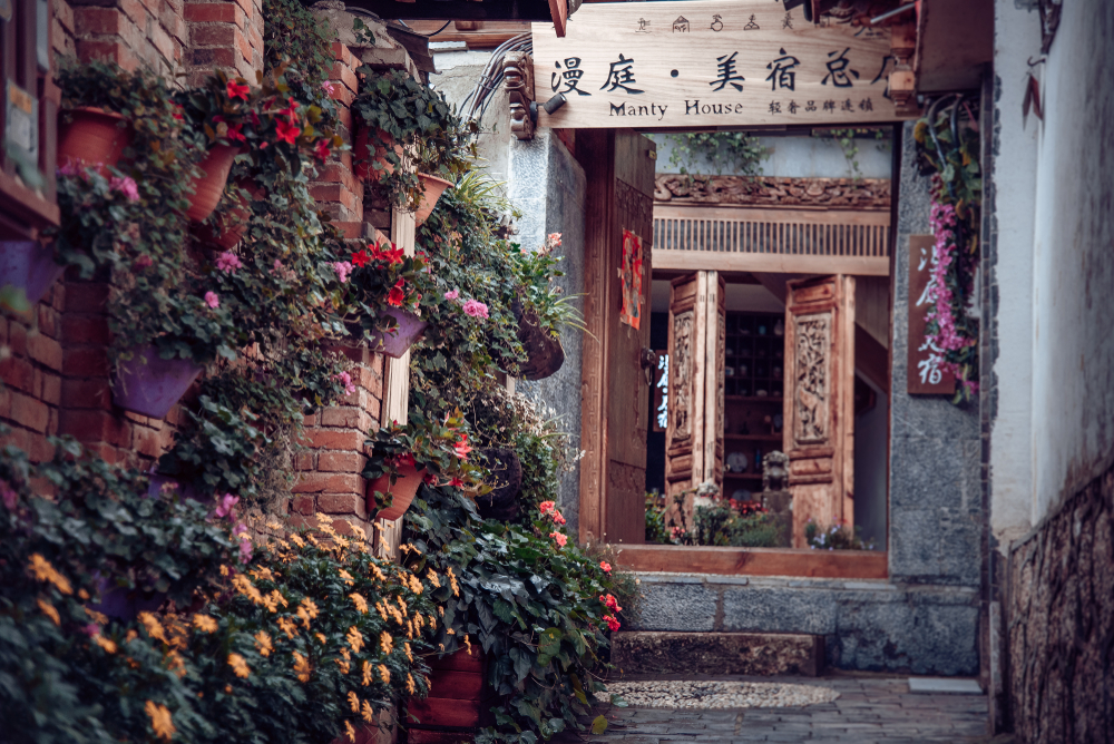 picturesque chinese guesthouse with flowers outside and a decorated wooden door