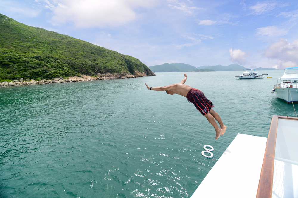 boat in blue waters off the coast of hong kong with man jumping off