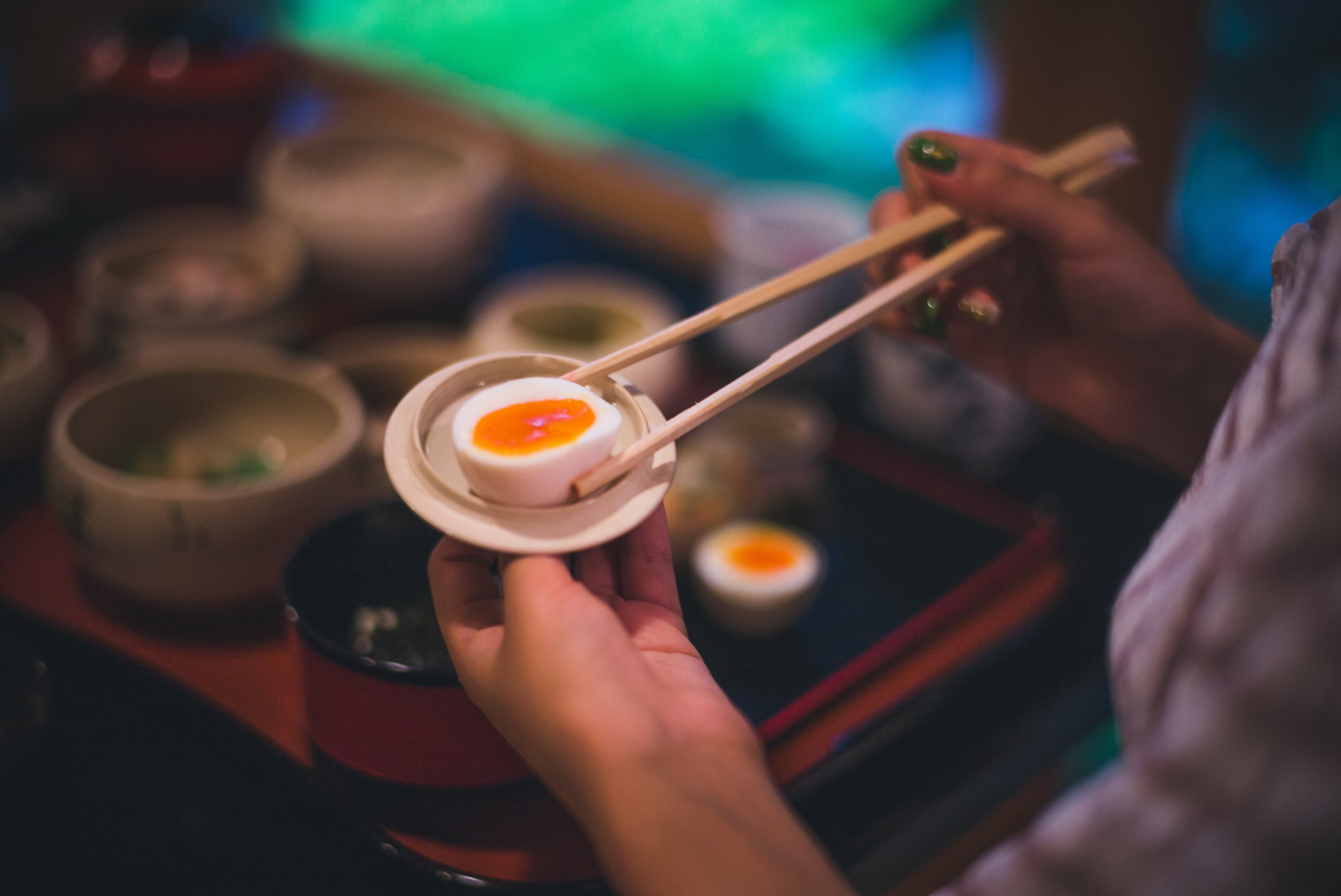 hardboiled egg on a small plate being held with chopsticks