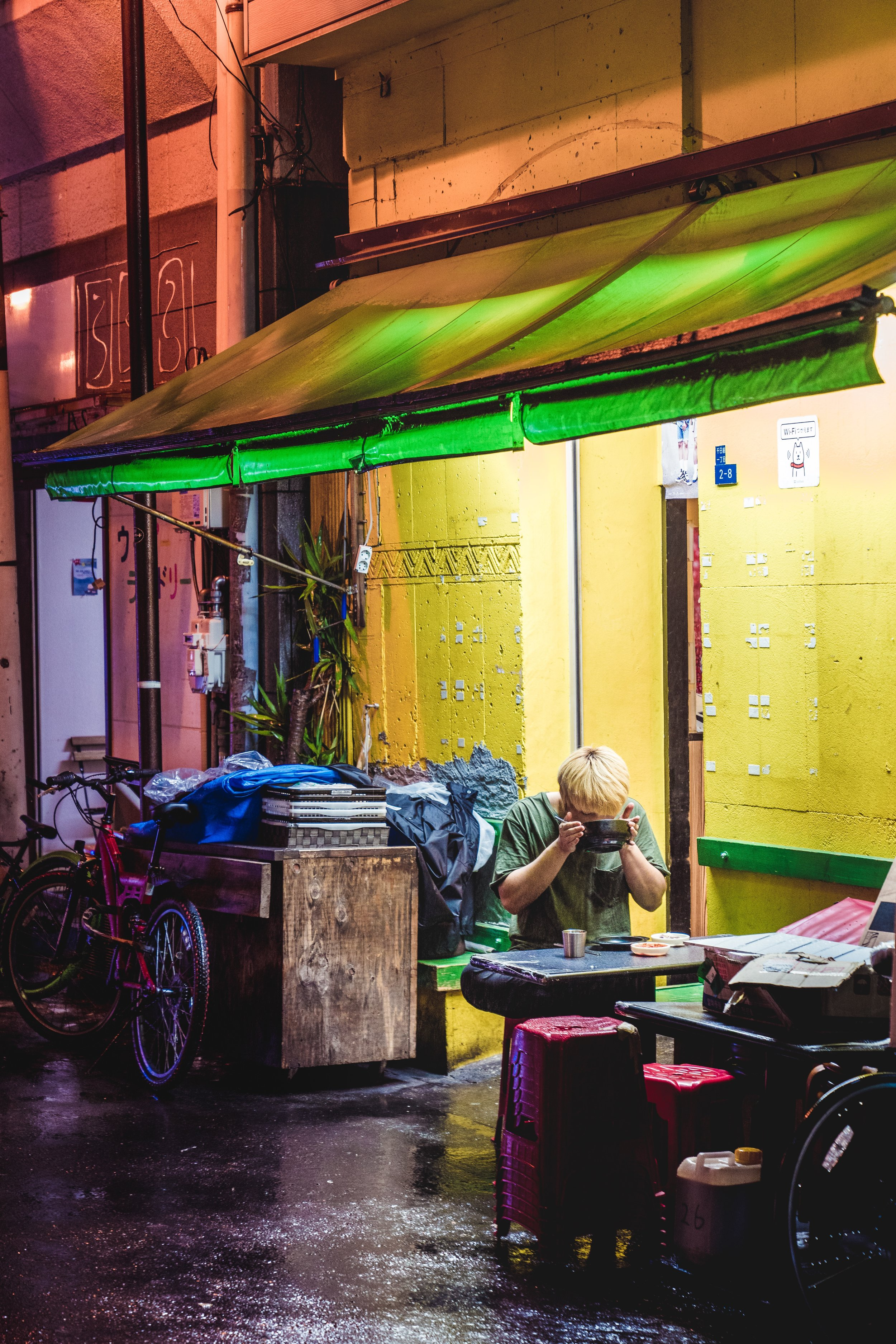 person sitting alone at a street stall eating soup