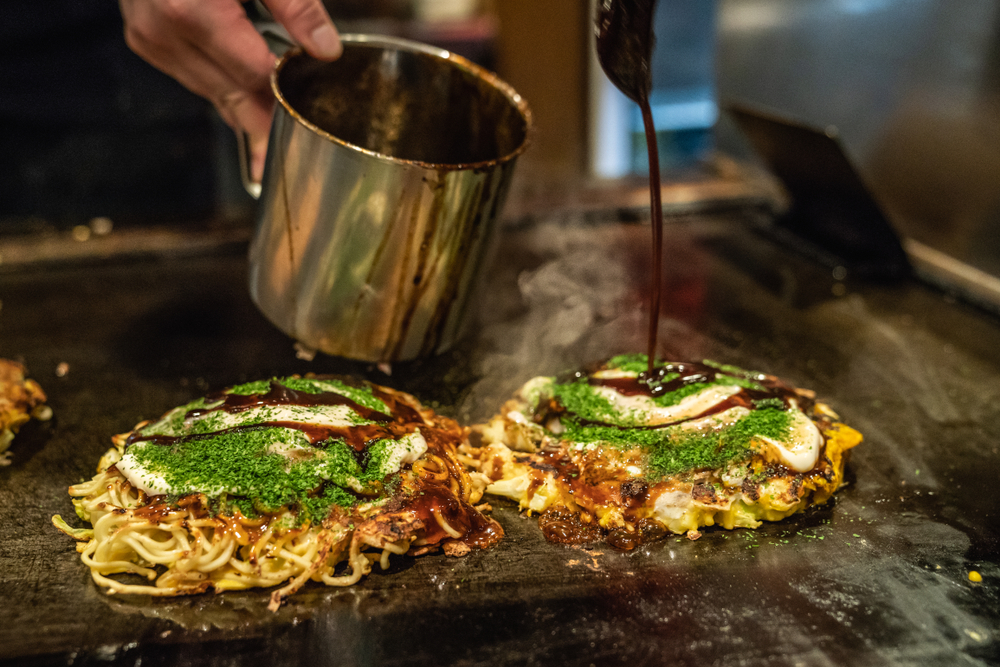 fried noodle okonomiyaki dish on griddle with sauce being poured over top