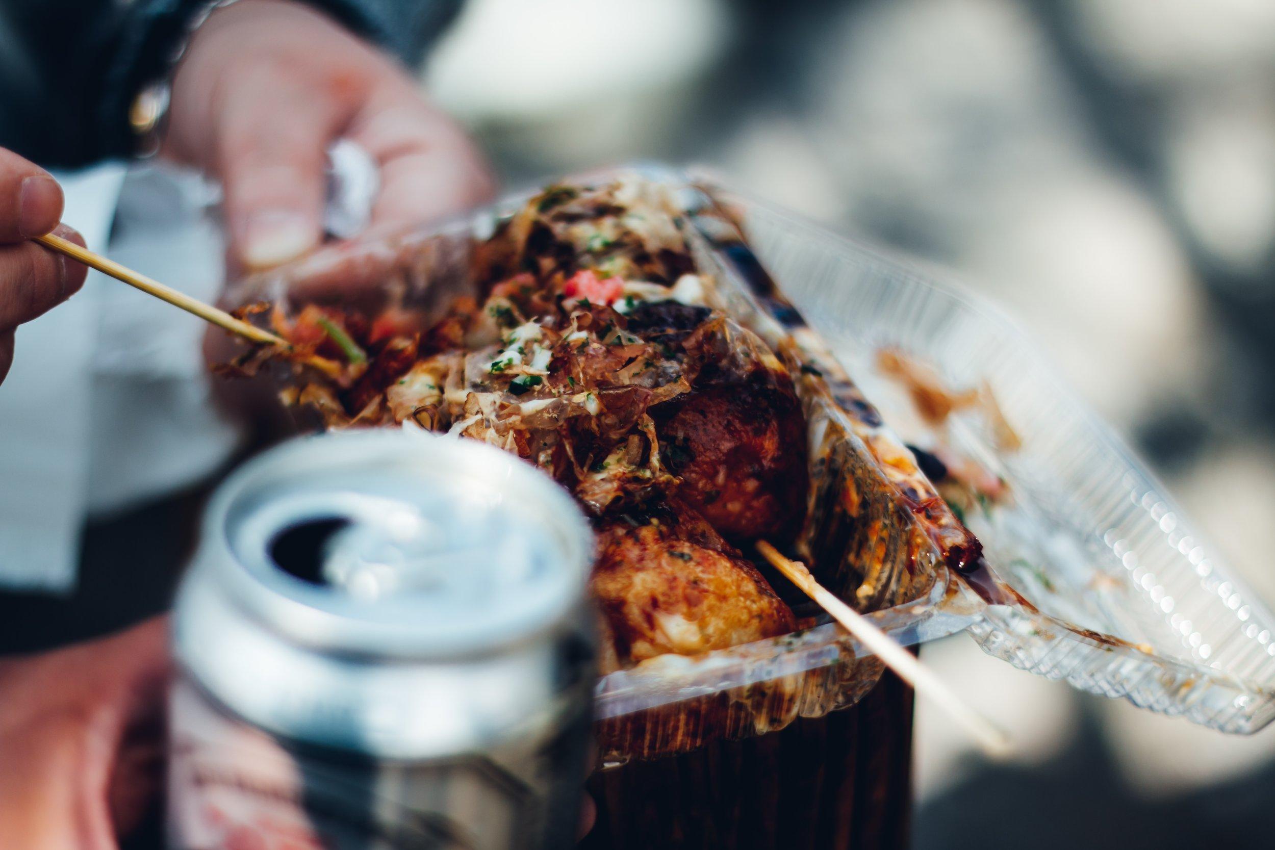 takoyaki dish being eaten next to a beer