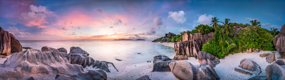 idyllic beach with large boulders and green jungle at sunset