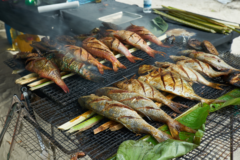 fresh fish being grilled over banana leaves