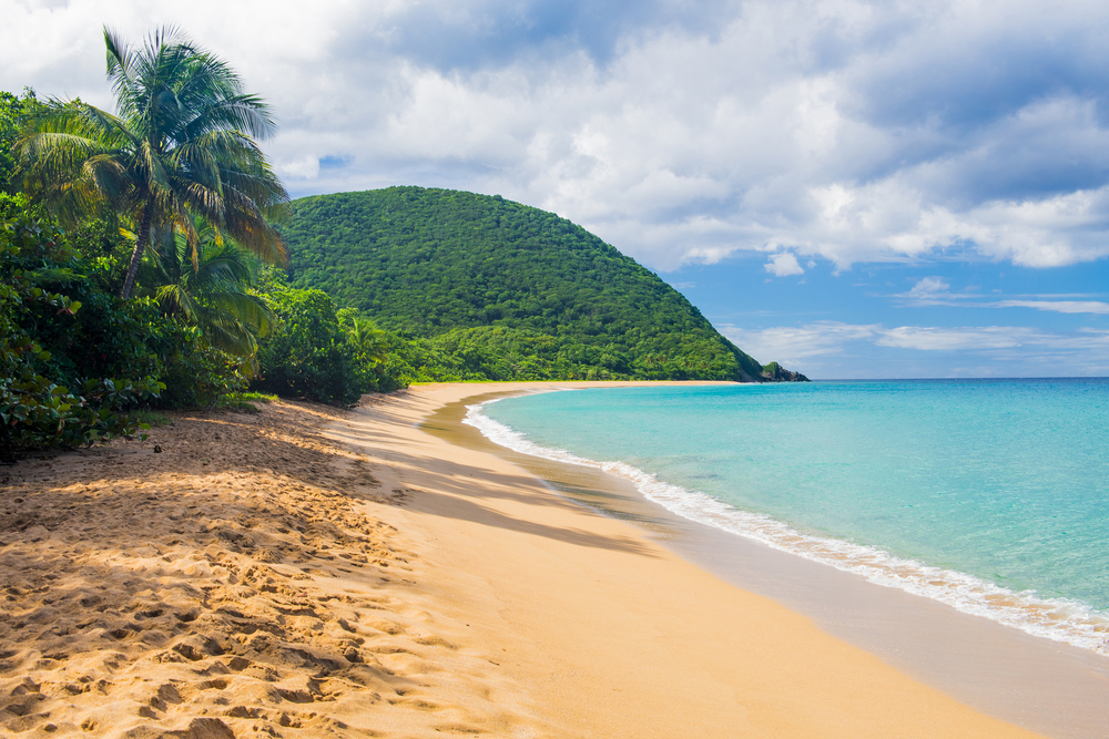 empty tropical beach with lush hills in the background