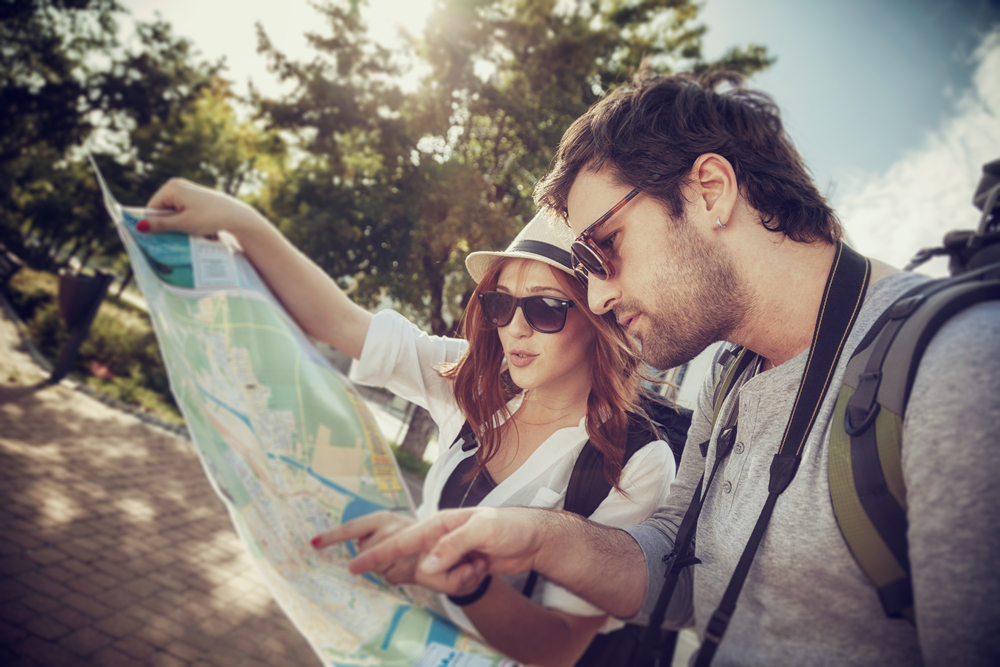 tourist couple looking at map together