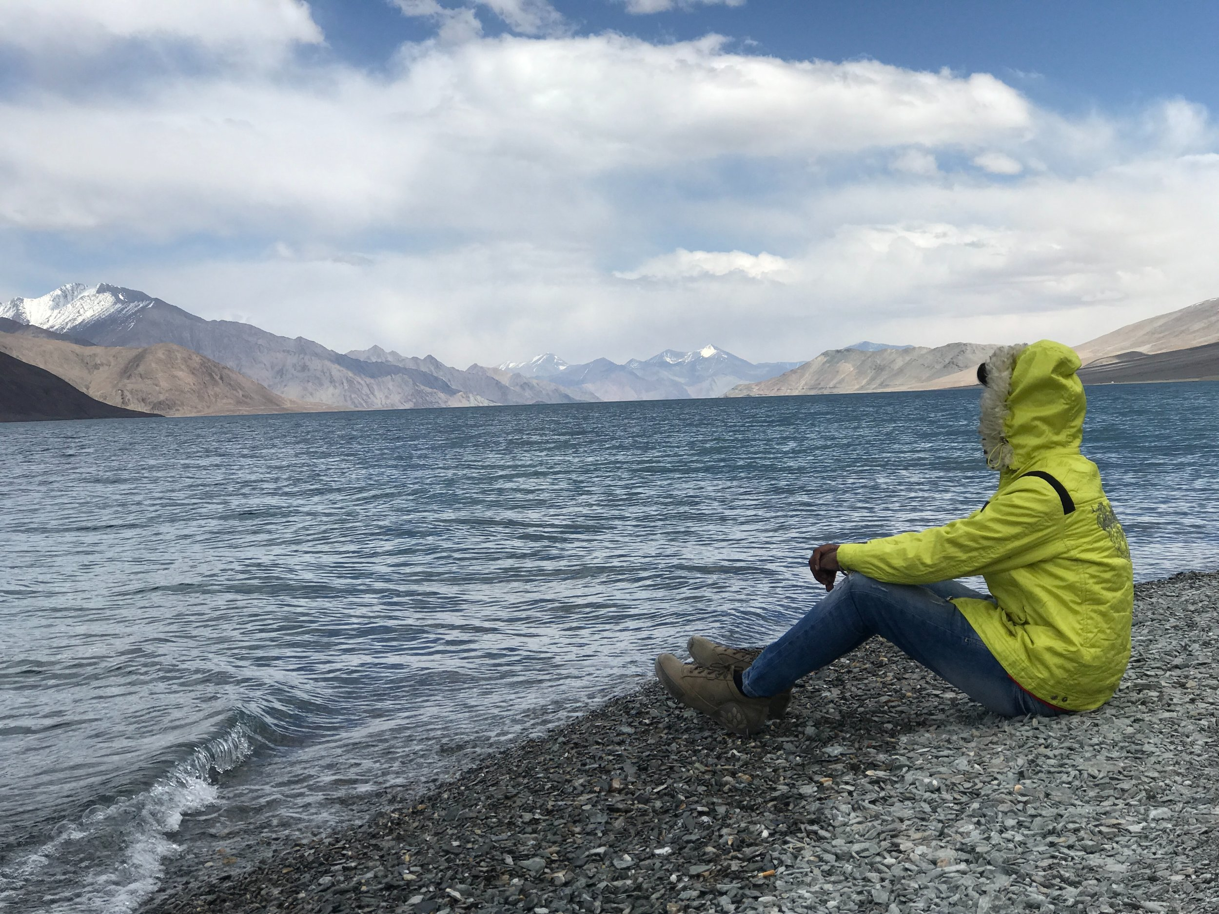 solo traveler sitting on the edge of a glacial lake