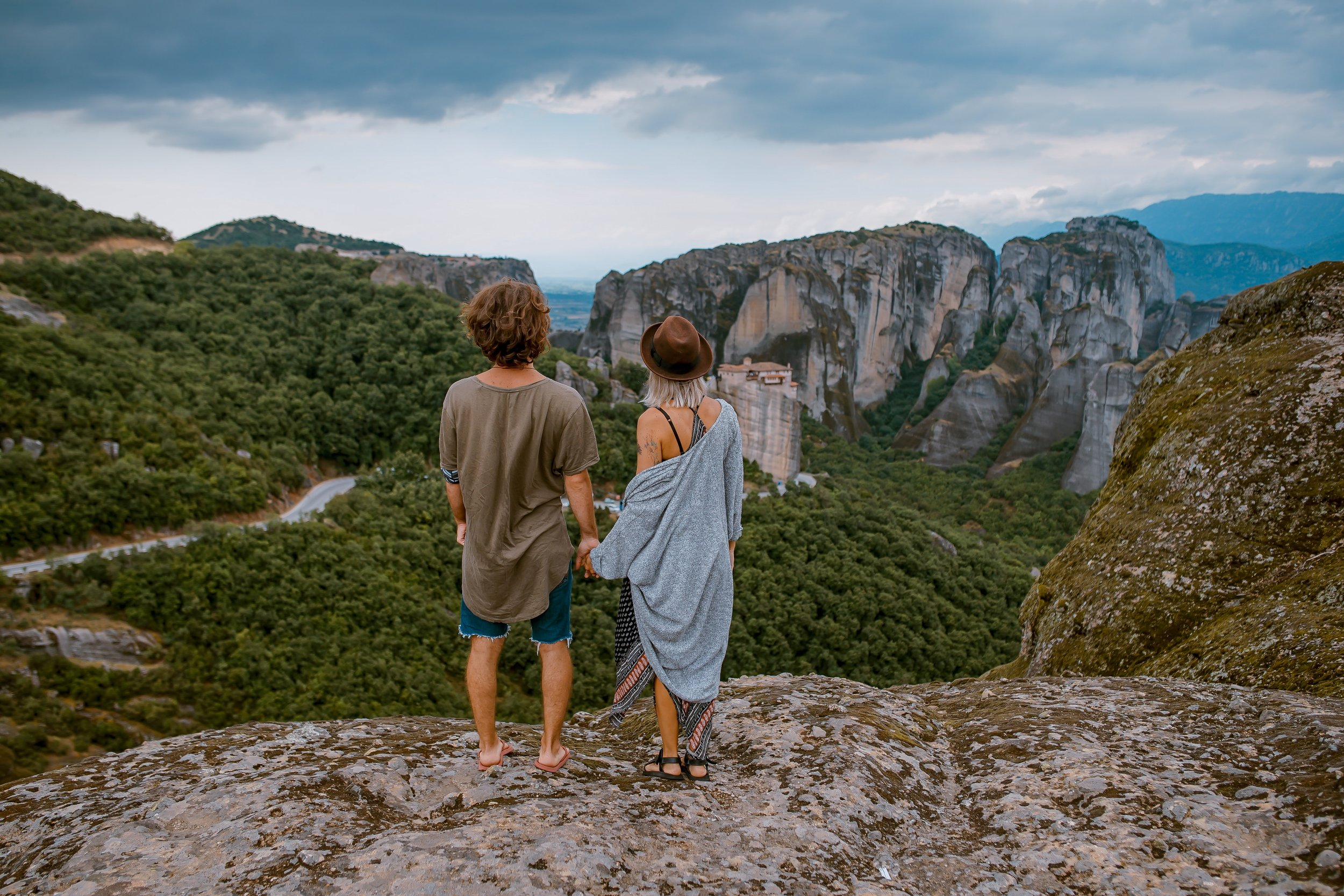 couple holding hands on the edge of a cliff overlooking the landscapes below