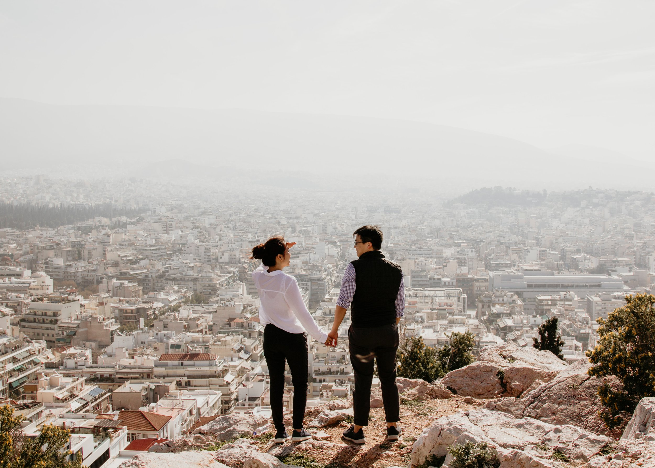 couple holding hands on a cliff overlooking the city below