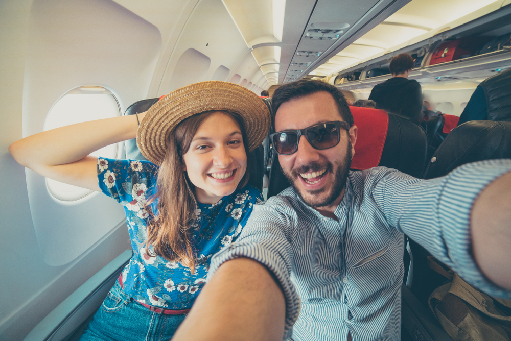 couple taking a selfie on the airplane during flight around the world