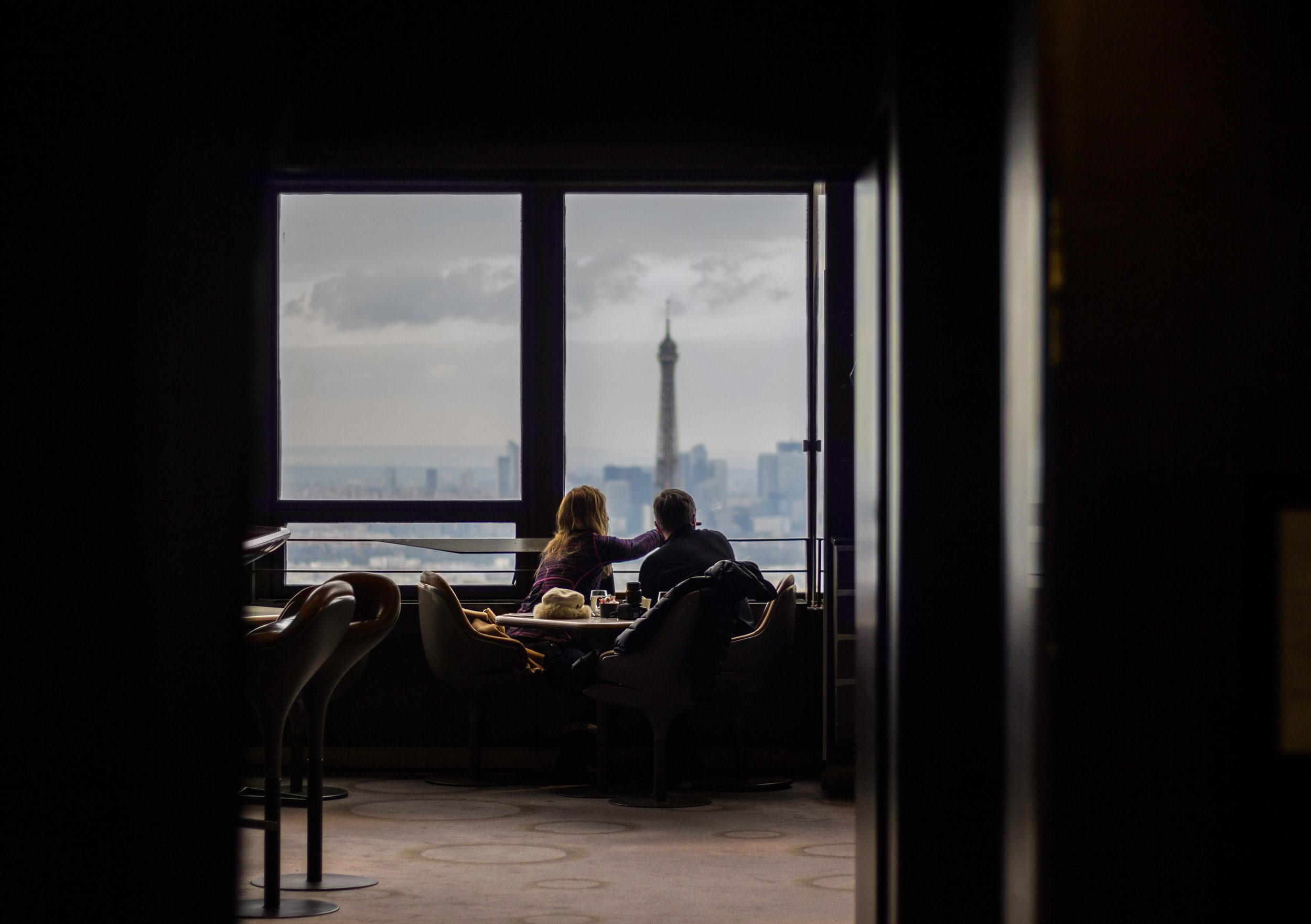 couple looking out hotel window at downtown paris france