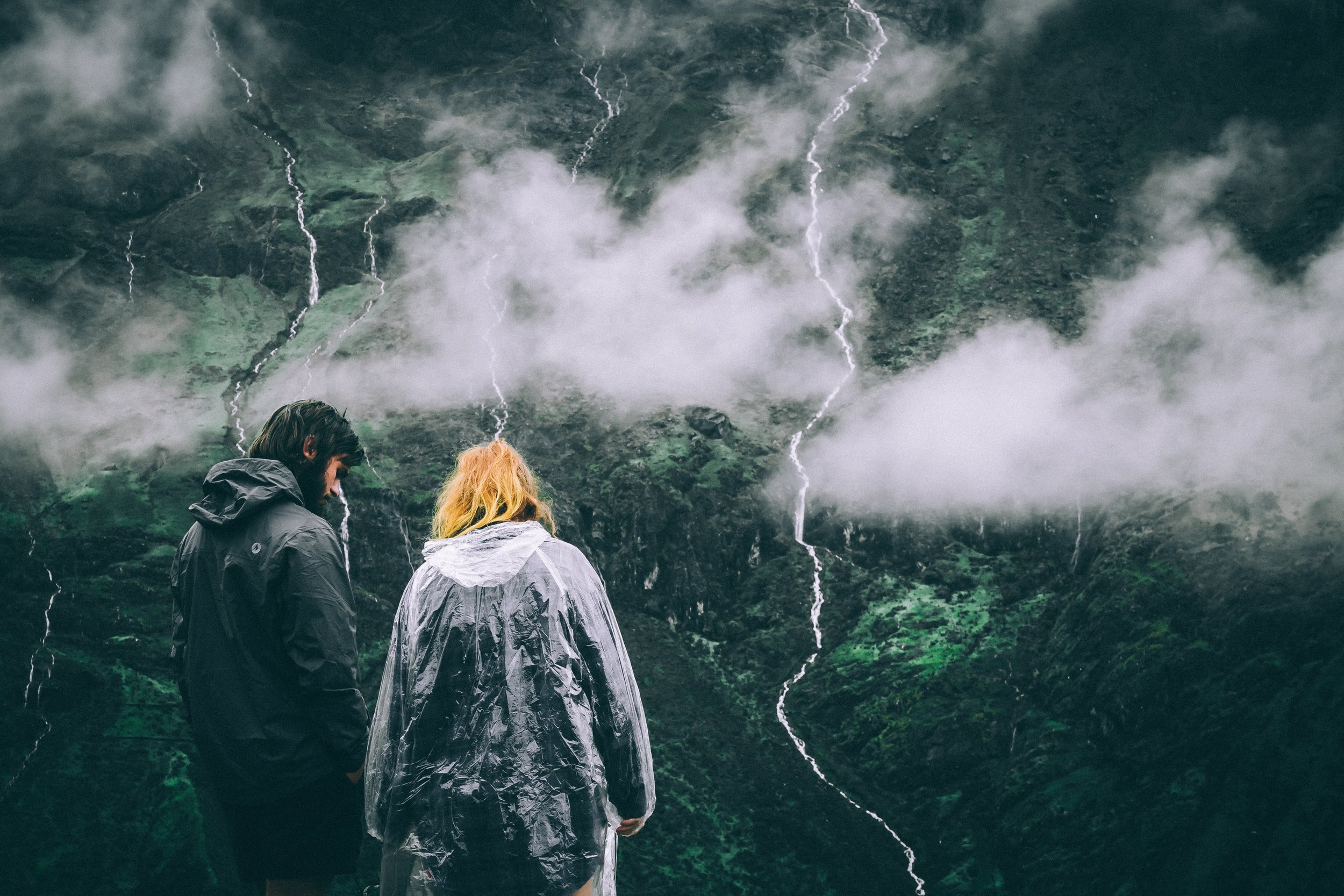 couple in rain ponchos surrounded by lush green landscapes in peru