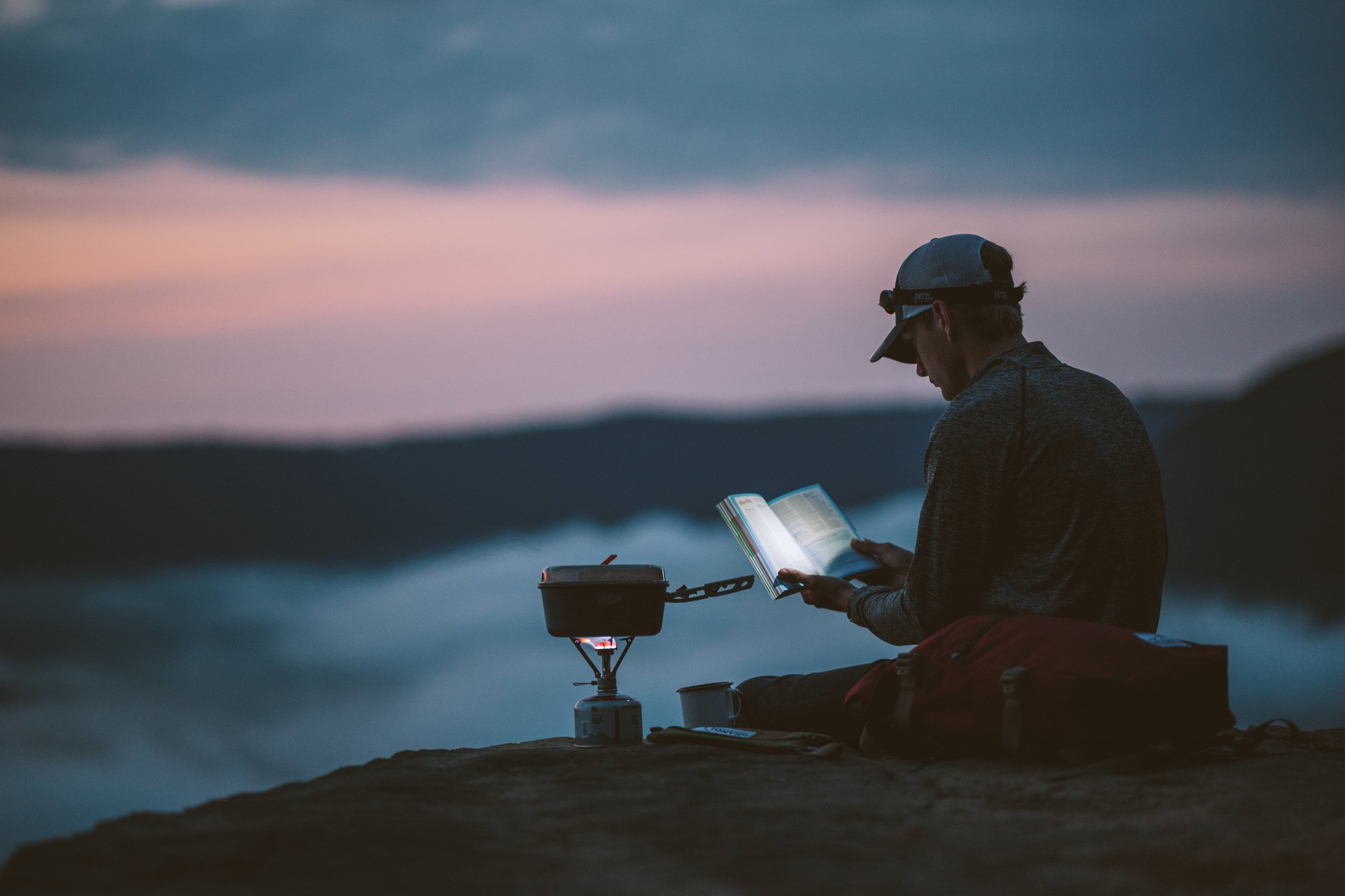 man reading book in nature with a headlamp for light