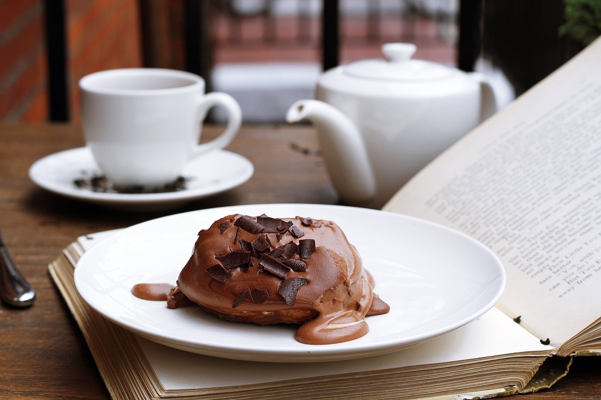 table with chocolate pastry, tea, and a book