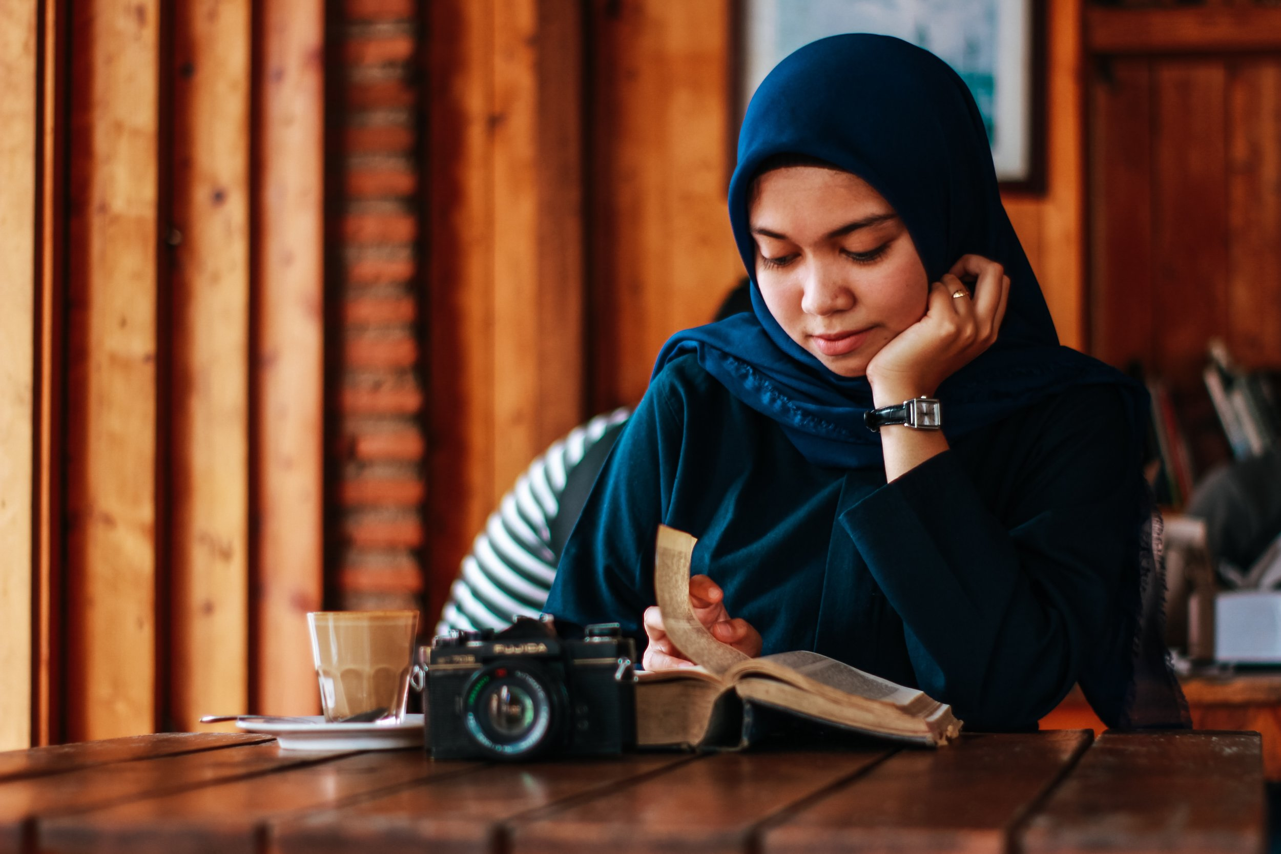 woman reading a book in a cafe with coffee