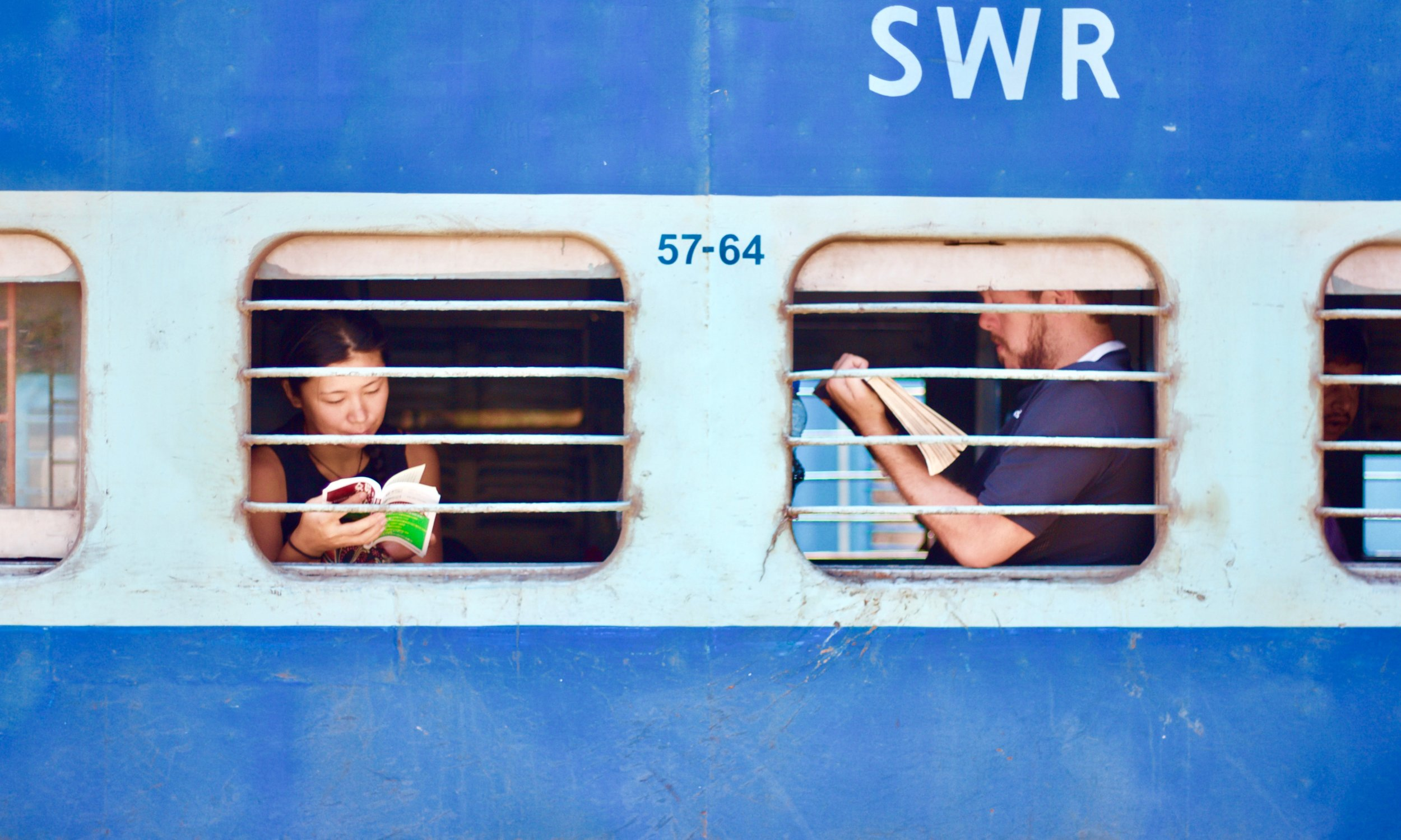 people reading in the windows of a train in india