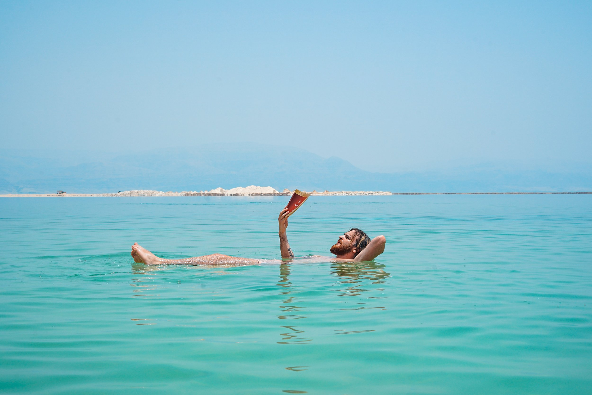 man floating in turquoise water reading a book