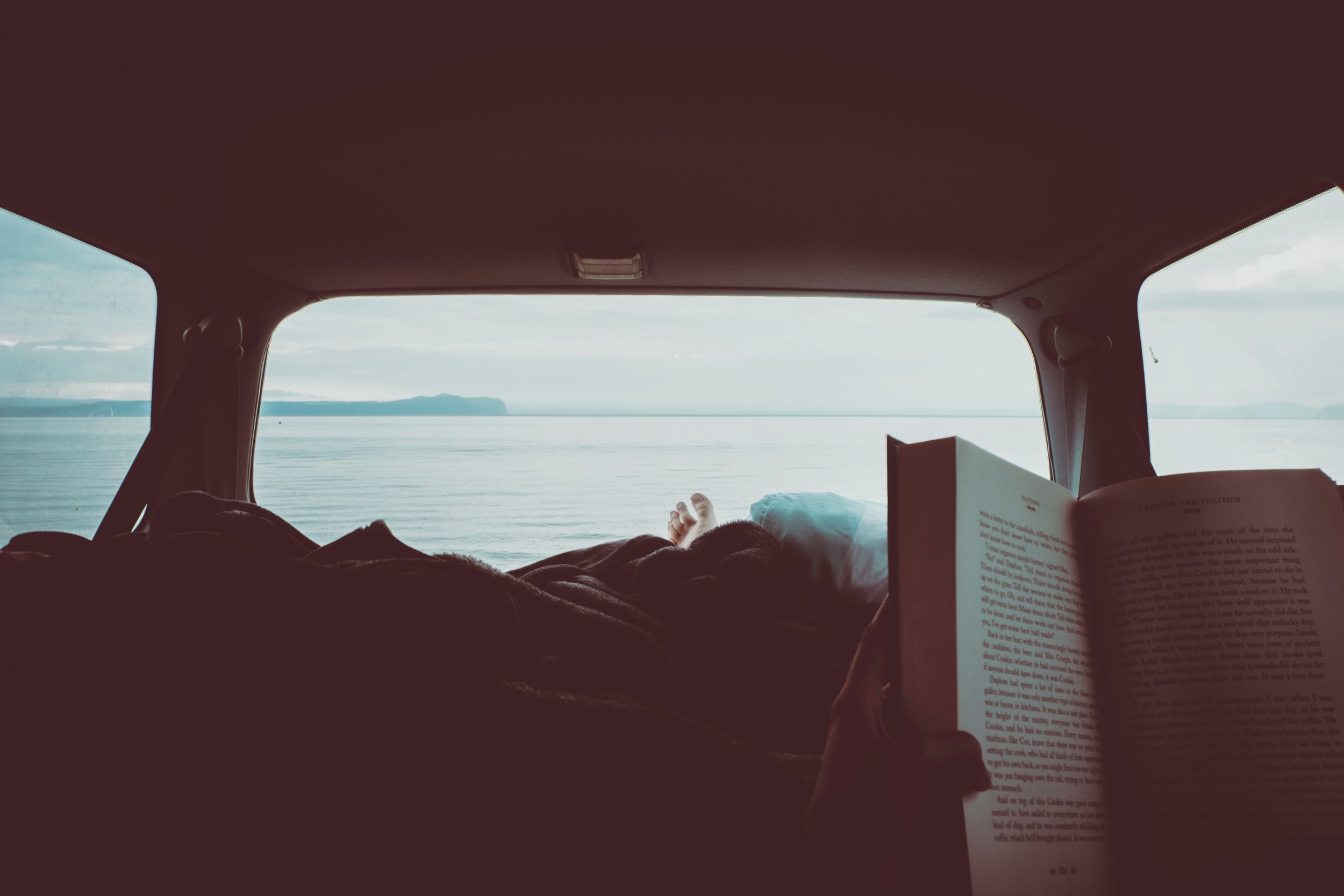 person reading a book while laying down in the back of a camper van
