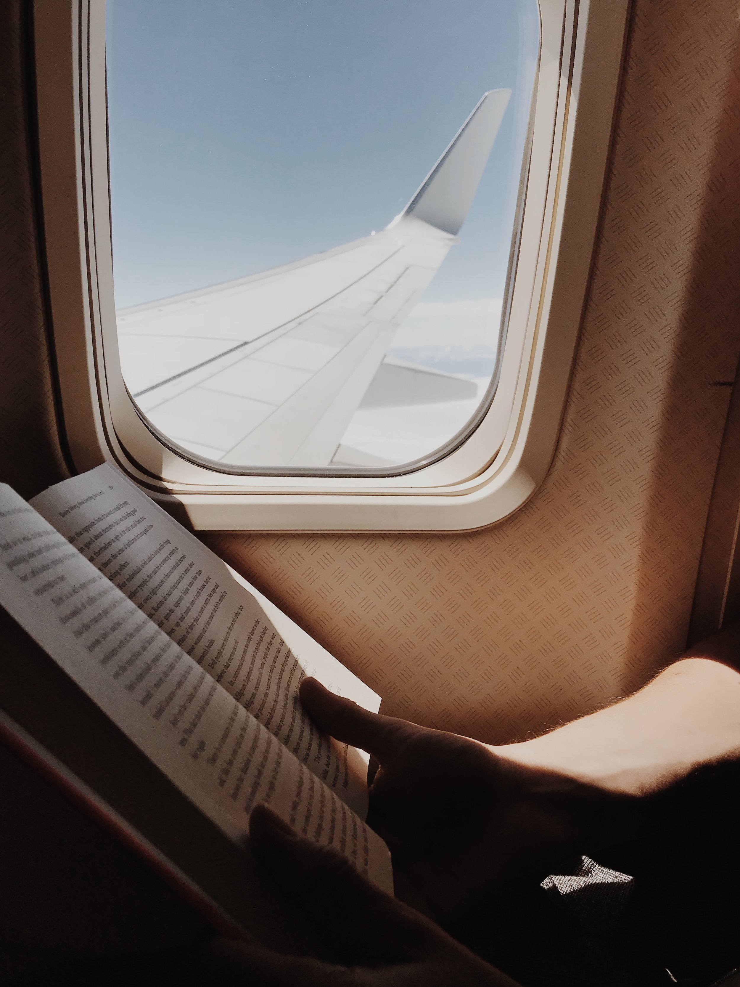 person reading a book next to the window on an airplane
