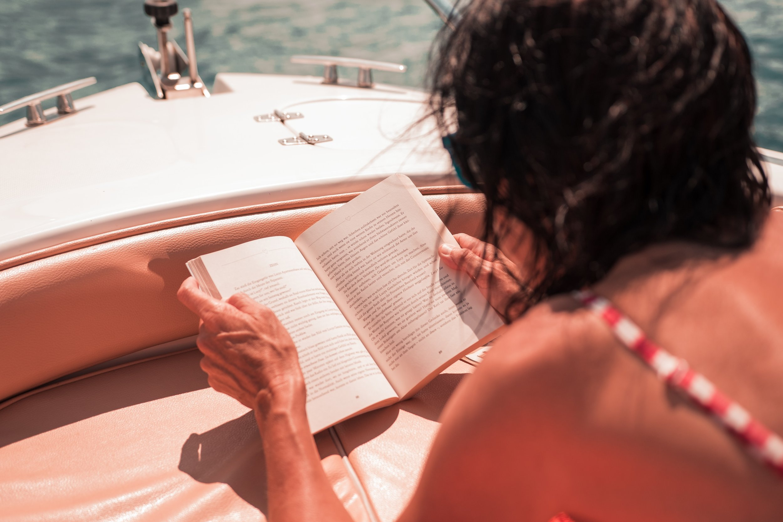 woman reading a book while laying in the sun on a boat