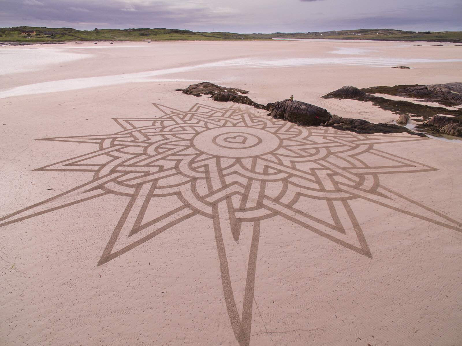 MOST SURPRISING LOCATION  (Ireland) In Ireland I found a beach that acts as a road between the mainland and a tidal island. The span was enormous and I could complete two huge works during one low tide. Artwork: 'Celtic Star.'