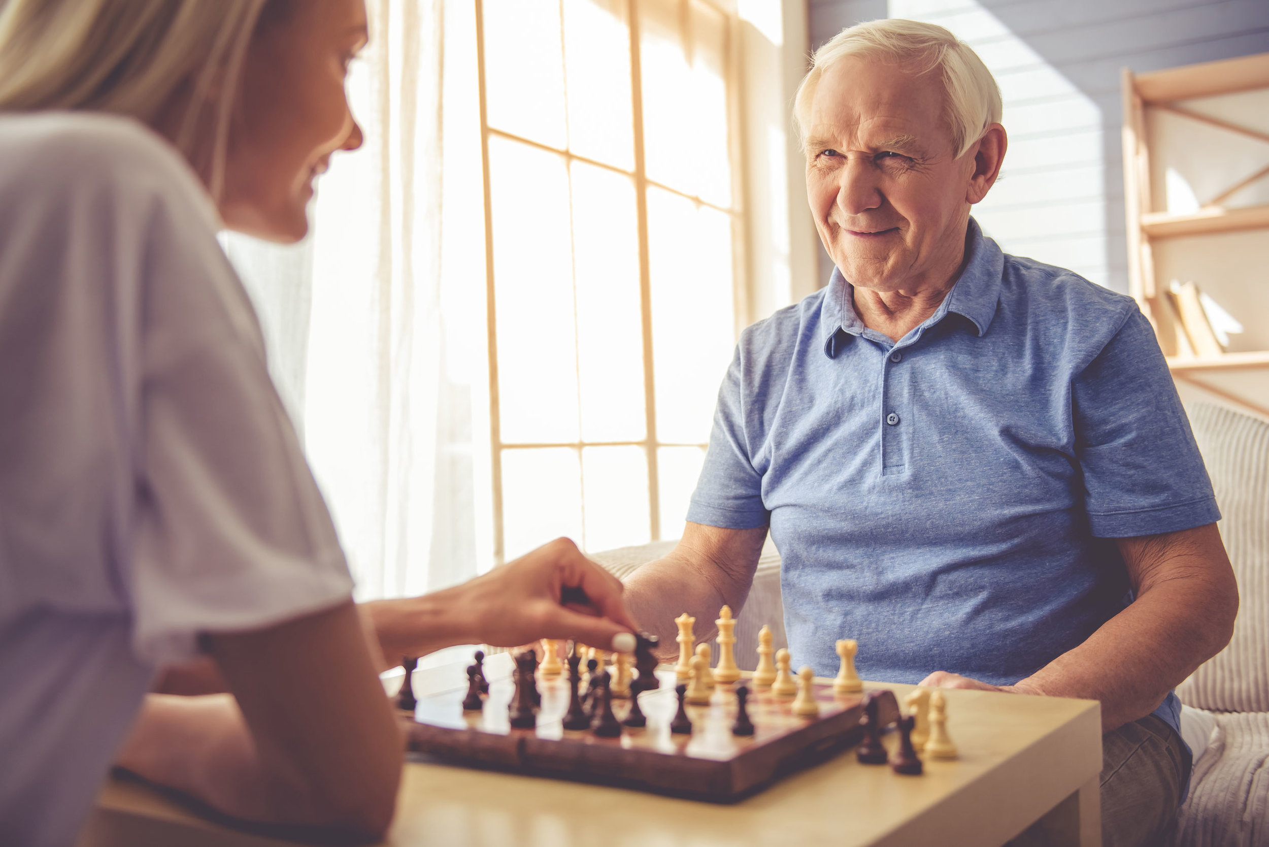 63888907 - beautiful young girl-volunteer and handsome old man are playing chess and smiling