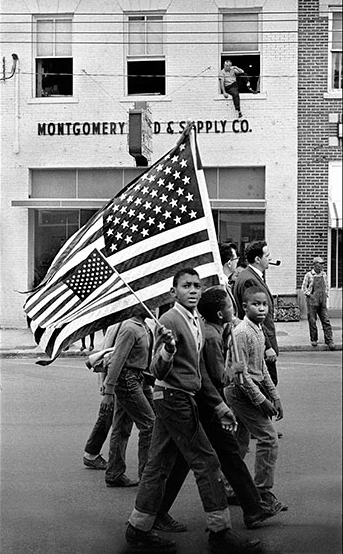 """Photo:""""Young Civil Rights Marchers in Montgomery March With American Flags""""by Stephen Somerstein."""