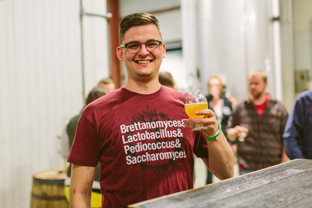 A beer enthusiast lists his microbial brewing partners on his shirt.