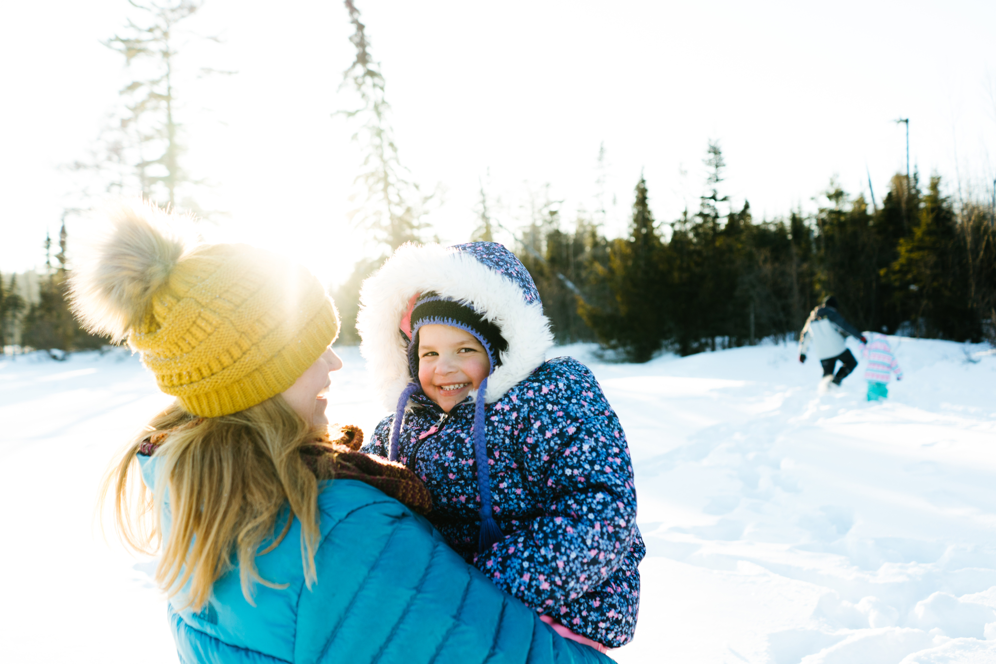 Mother and Daughter play in the snow in winter
