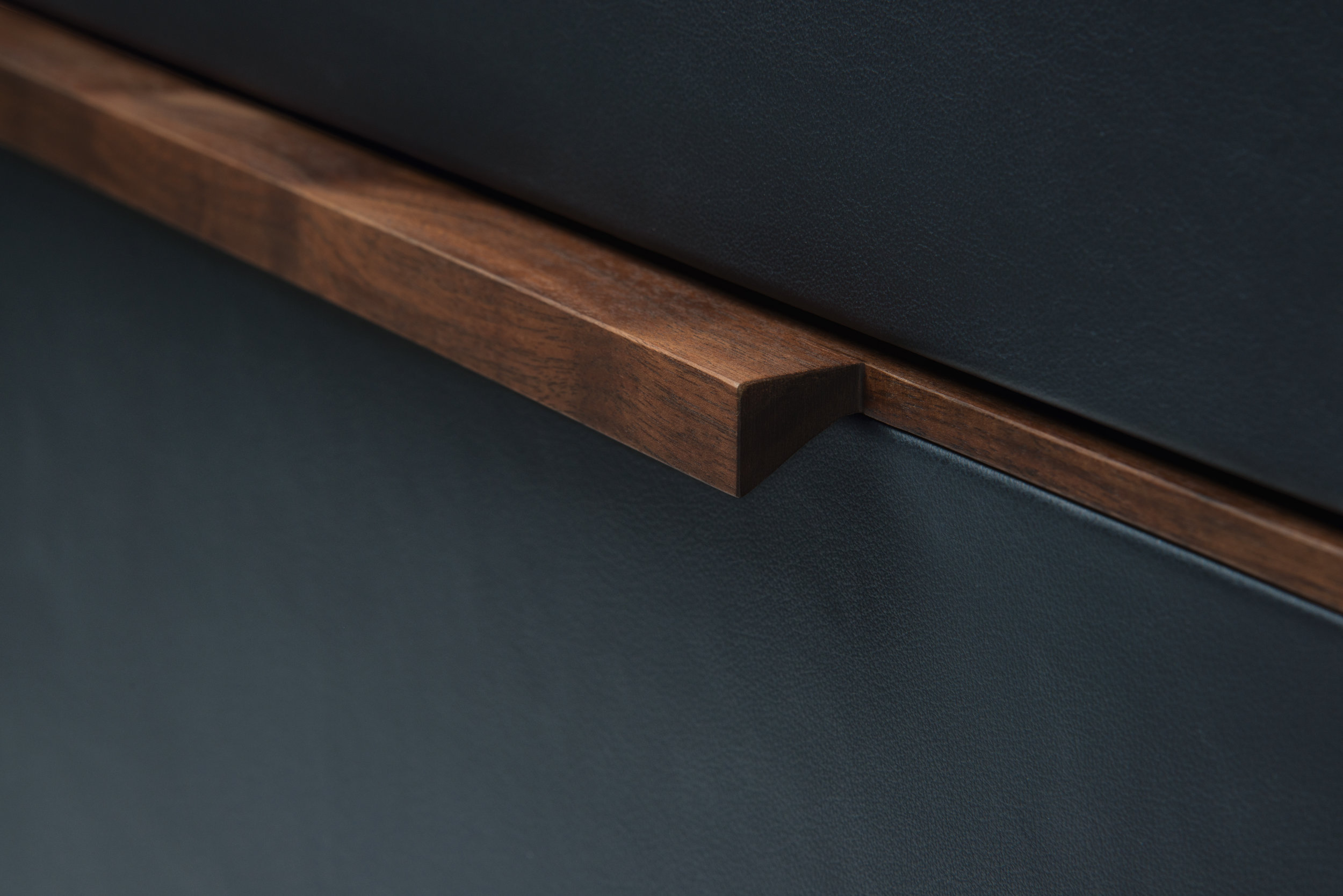 > Detail of pulls on leather-wrapped drawer fronts.