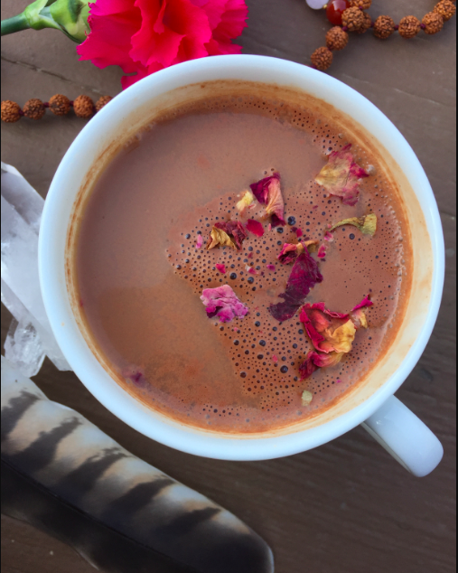 image of cacao elixir drink with rose petals sprinkled on top