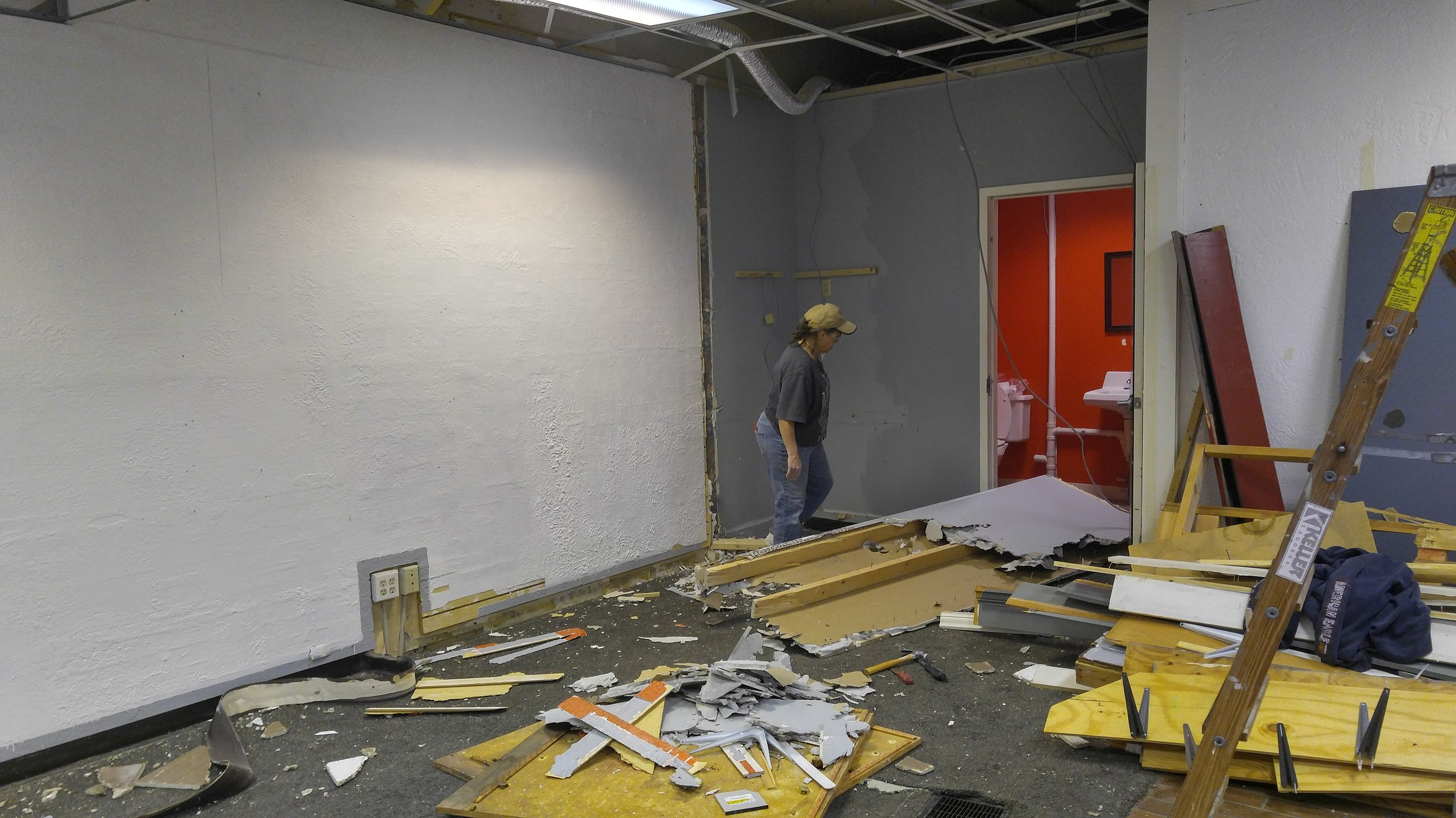 Tearing down a partial wall in order to improve flow of foot traffic to the restroom.