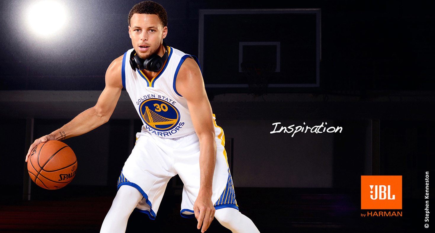 advertisement photo of Stephen Curry in his white uniform bouncing a basketball in dark gym setting with the ad words Inspiration JBL by Harmon