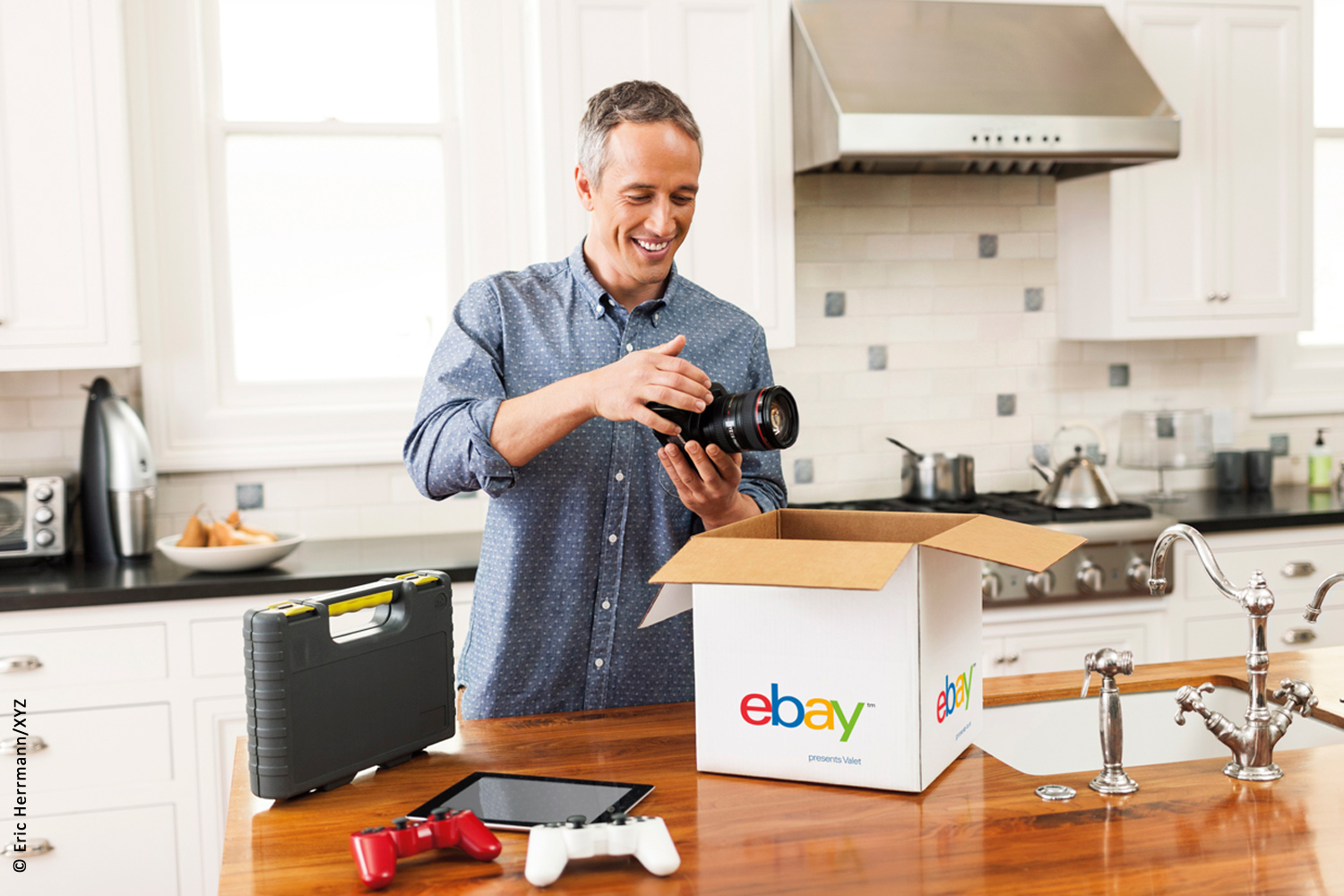 photo of smiling man standing behind kitchen counter putting camera into an ebay valet shipping service box