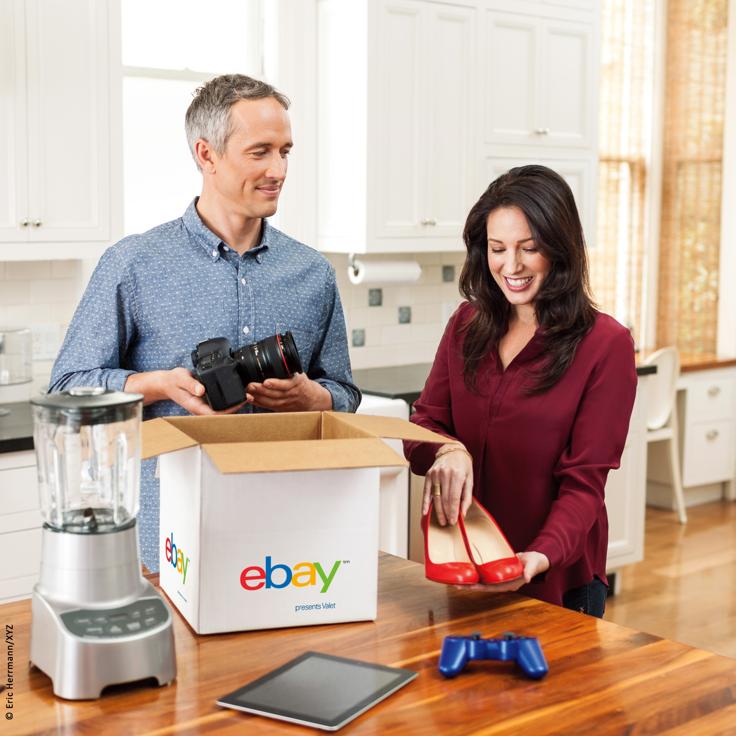 photo of smiling women and man standing in their kitchen packing a camera, blender, high heel shoes , ipad into an eBay valet shipping service box