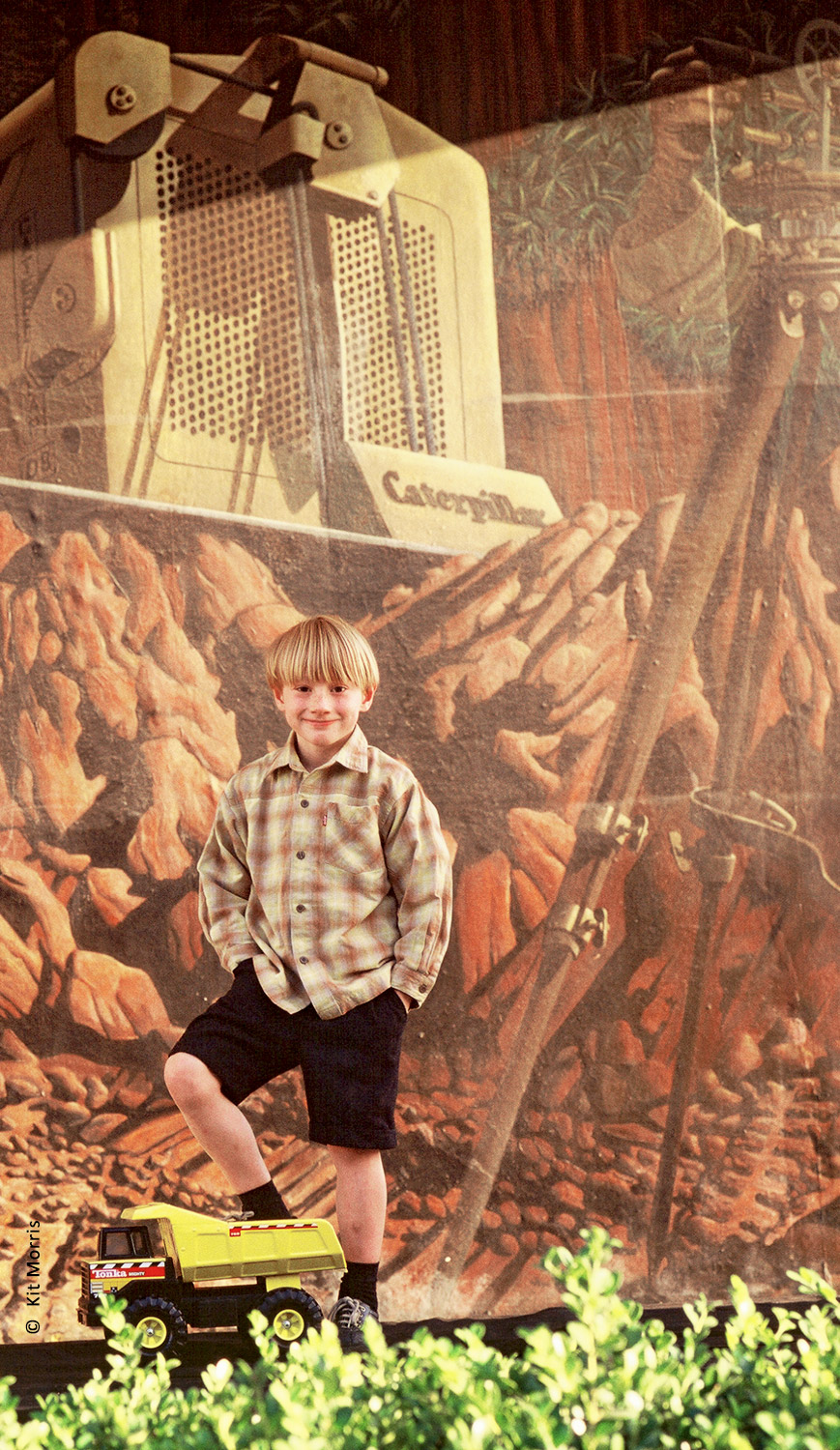 photo of young boy wearing a plaid Levi's shirt standing on a toy Tonka dump truck in front of a painted mural of a construction site