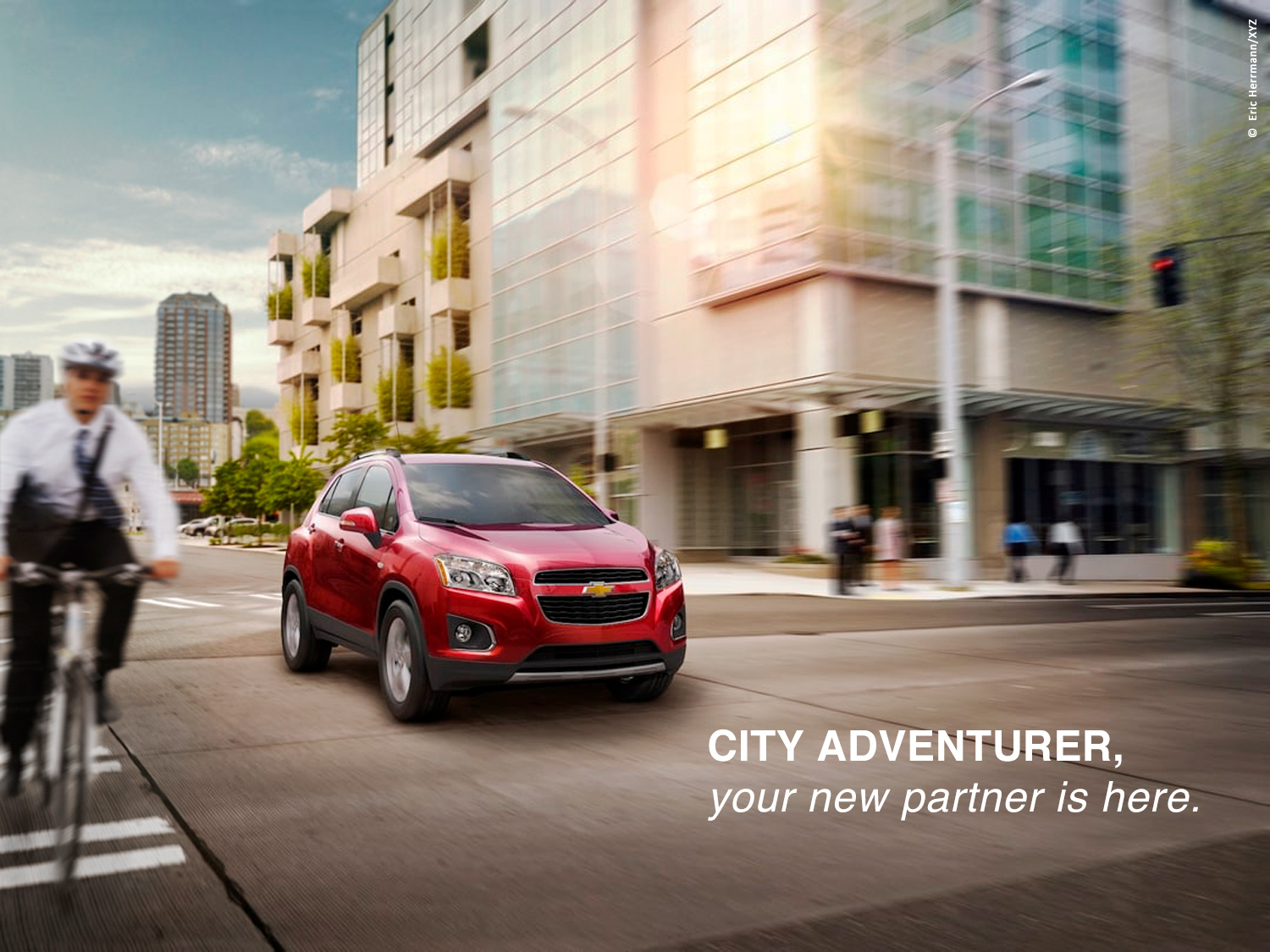 photo of modern apartment building on a city street with a man commuting on a bike next to Chevy Trax car
