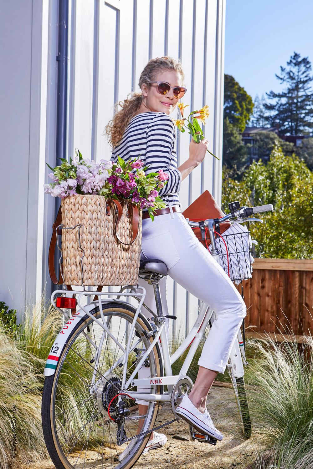 Photo of outdoor summery location of a beautiful model with the woven basket on the back of her bicycle filled with fresh flowers