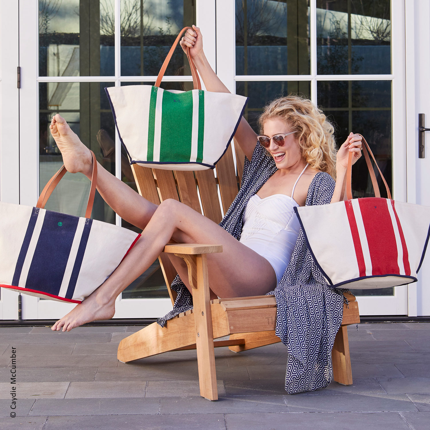 catalog shoot photo of laughing female model in a bathing suit sitting in a wooden chair holding three bold striped beach bags