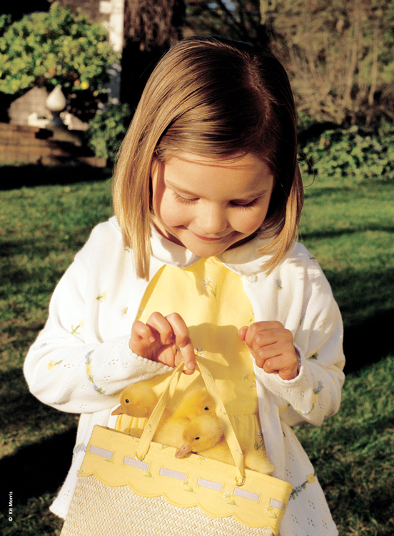 Photo of little girl dressed in Easter apparel holding a straw purse with three baby ducklings inside