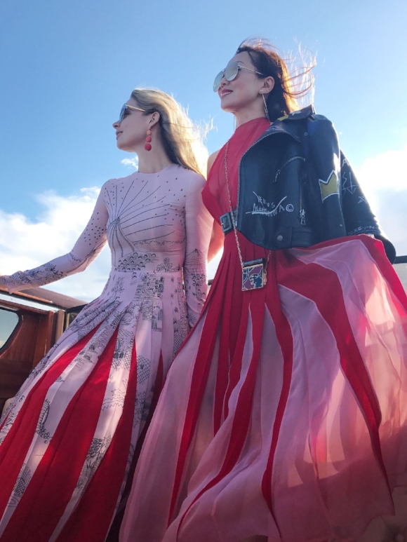 Arriving by boat with Tina Craig (right), dressed in Valentino.