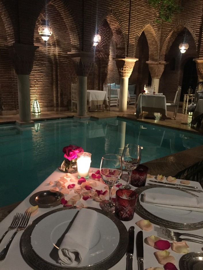 """Only Moroccans love roses more than we do. This was the setting for dinner in our hotel by the pool. The ceiling is open, revealing a night sky with candles and soft string music echoing throughout the Riad."""