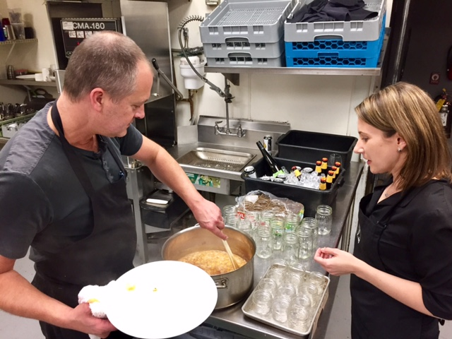Chef Paul and Raynette filling jars of peach jam