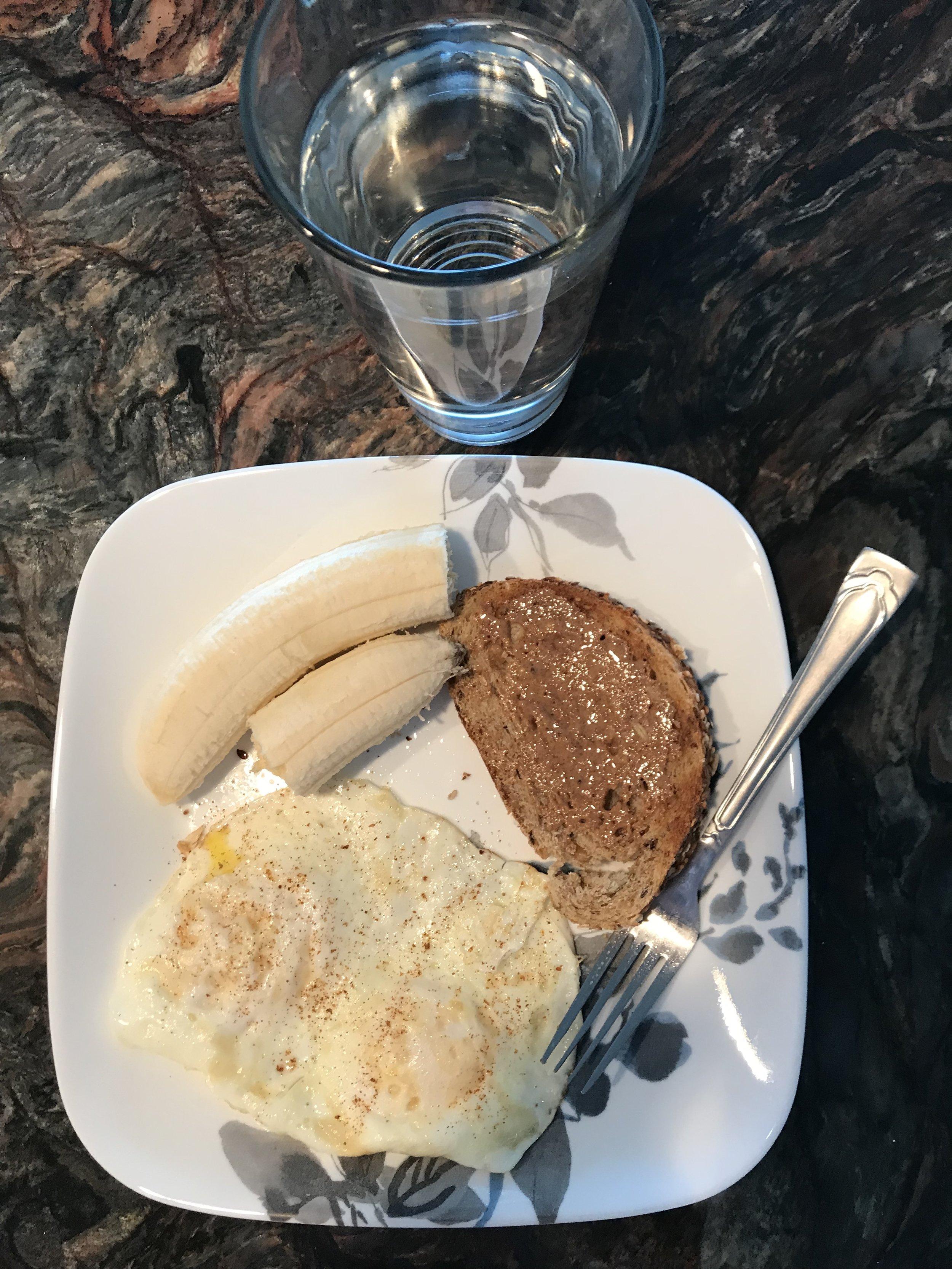BREAKFAST - 1 slice of multi-grain bread, 1 tsp of almond butter, 1 medium banana, 2 fried eggs, and water.