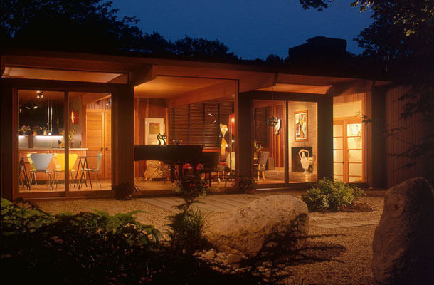 This is the view from the backyard, at night, showing the addition built in place of the sagging carport. The long floor to ceiling glass wall in the living room was bathed in air from a long vent for the in-floor heating. This made for a most comfortable glazed room with low-cost technology.