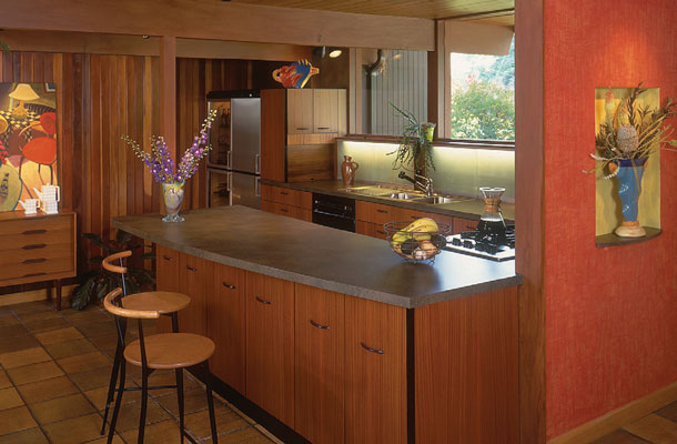 This photo shows the revised kitchen, almost like it was originally planned. Due to years of roof beams sagging, the long-span beams needed shoring up, so a partition with niche separating the entry from the kitchen was devised. An existing temporary post was incorporated into the new counter-top.