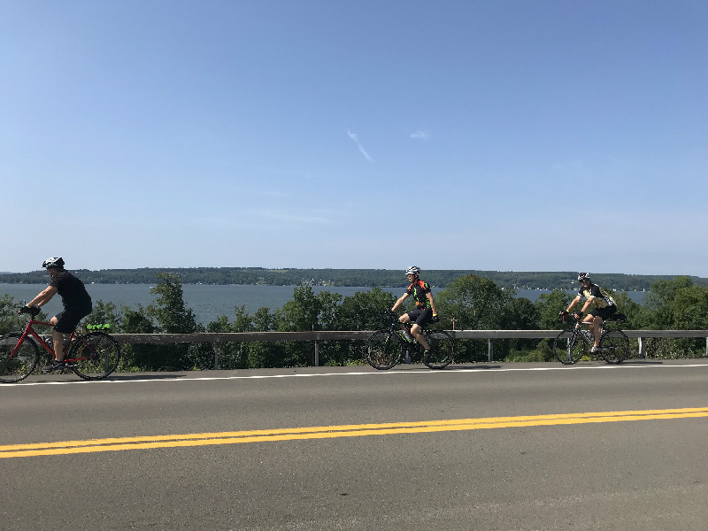 Bikers riding with Chautauqua Lake in background
