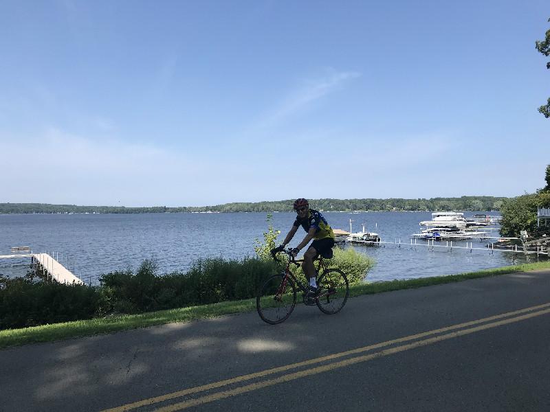 Biker riding near Bemus Point, NY with Chautauqua Lake in background