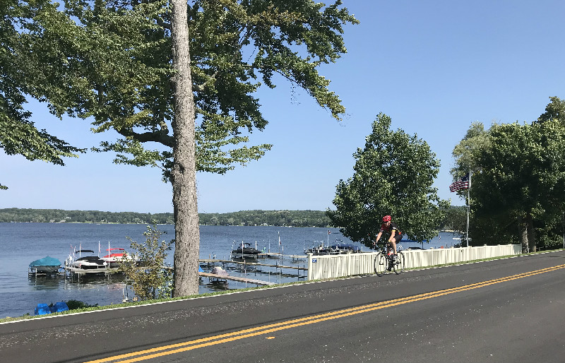 Biker riding in Bemus Point, NY with Chautauqua Lake in background