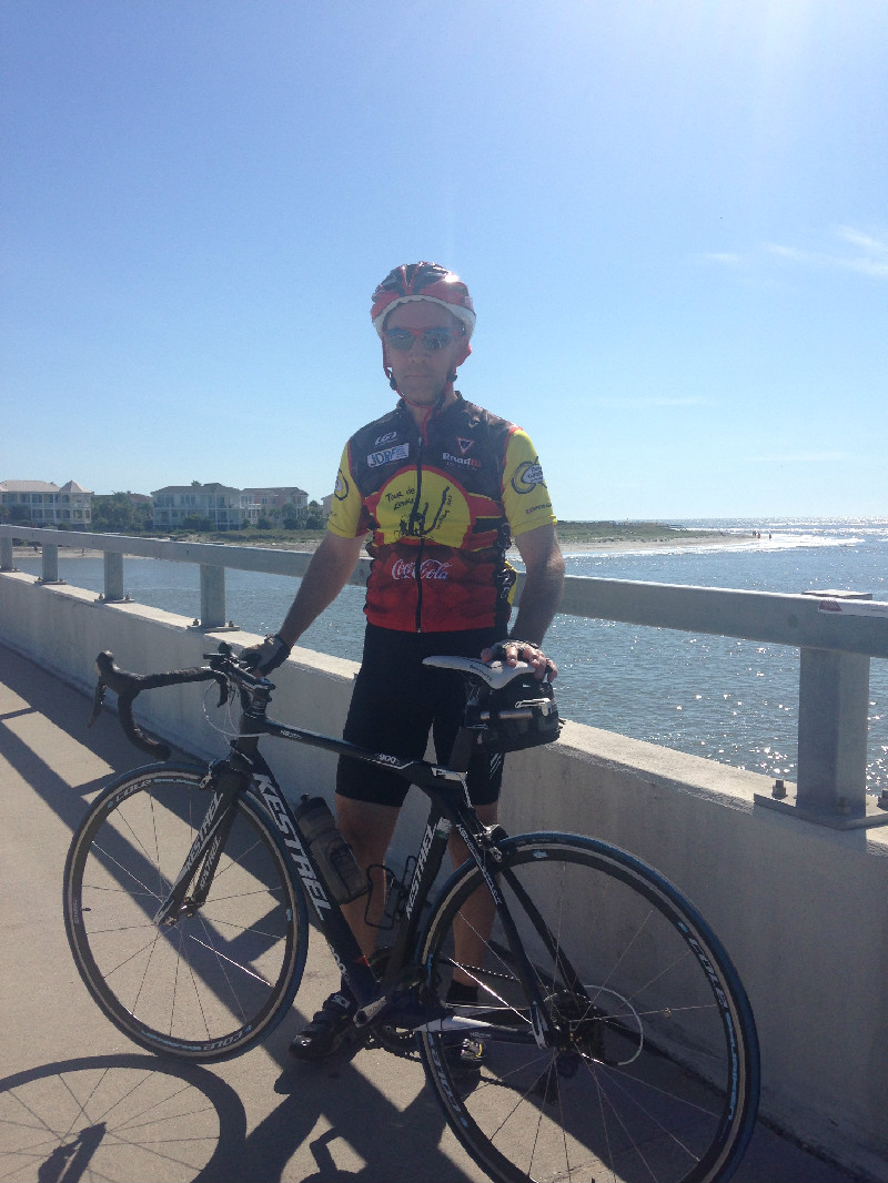 Picture of man standing with bicycle on bridge with the Atlantic Ocean in background